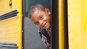 Boy looking back after boarding school bus