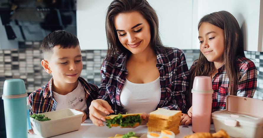 Una madre hispana prepara una comida con su hijo y su hija.