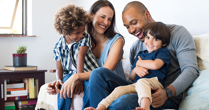 A mixed race family with adopted children has fun at home.