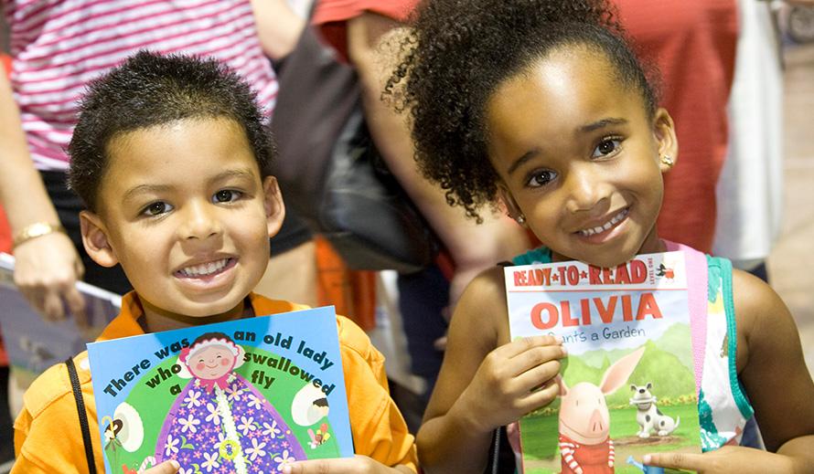 Niño y niña sonriente, cada uno sosteniendo un libro.