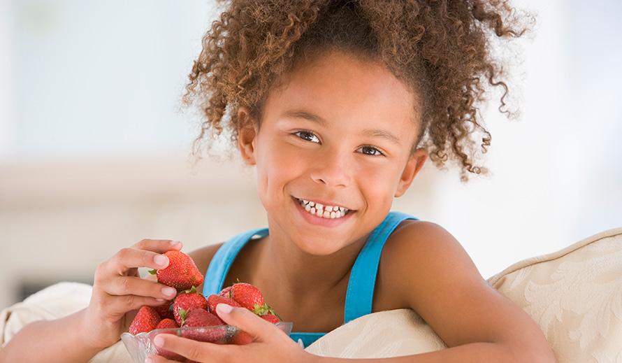 Niña comiendo fresas