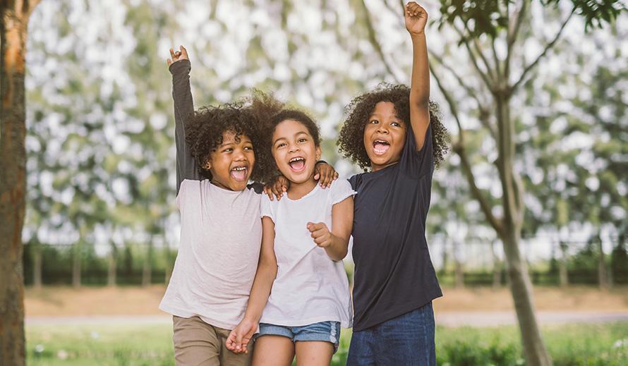 Trío de niñas felices, con los brazos en alto triunfantes.