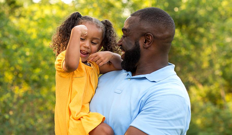 Papá sonriente con su niña pequeña en brazos.