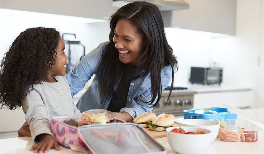 A mother and daughter prepare school lunch together.