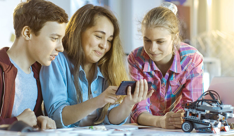 A mother reviews an app on her phone with her children.