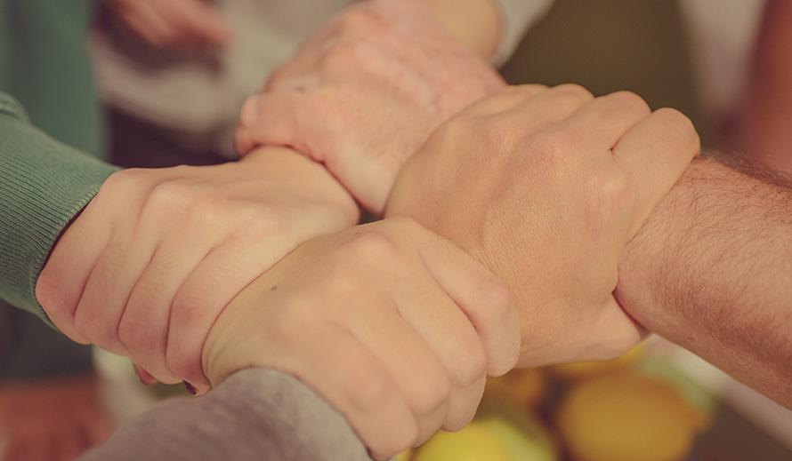 Four hands interlocking together on wrists.