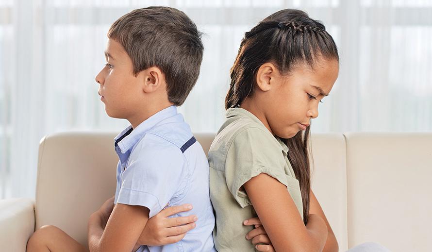 Hermano y hermana, enojados, sentados de espaldas con los brazos cruzados