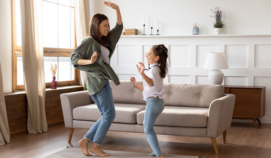 A mother and daughter dance inside to keep active.