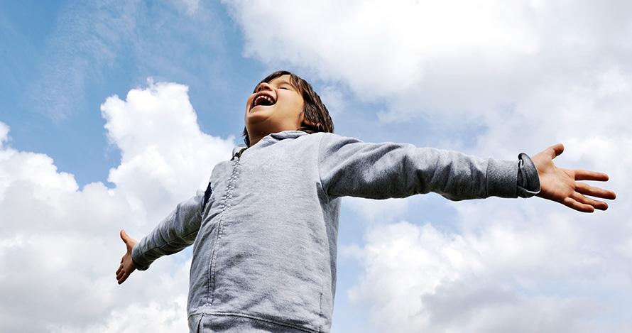 Un joven latino abre los brazos con alegría.
