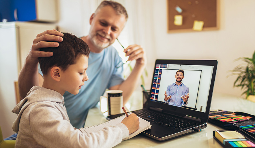 A father helps his son with his virtual studies.