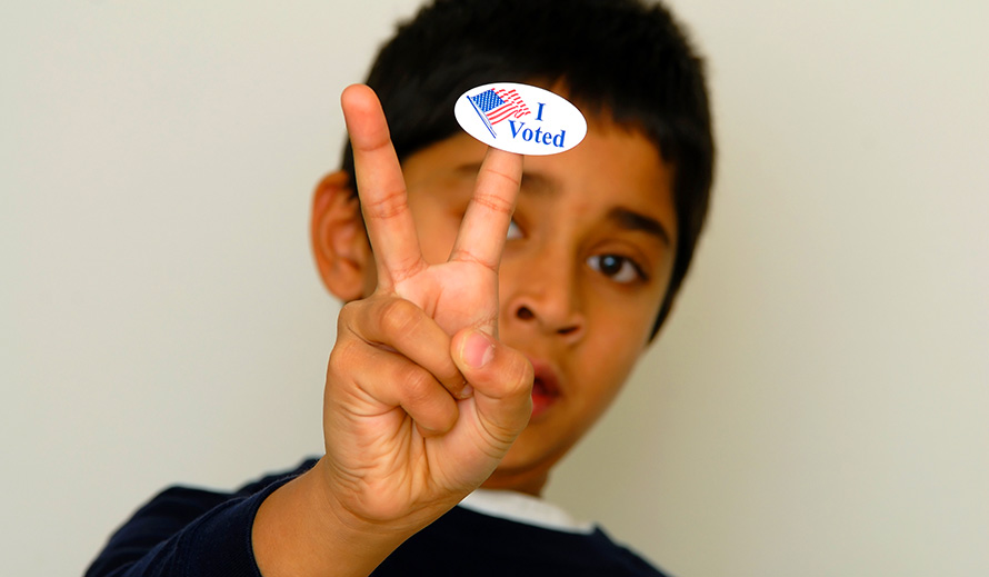 "Boy holding up ""I voted"" sticker peace hand sign"