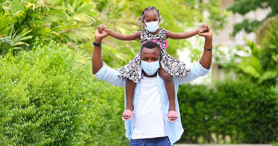 Yon timoun Afriken Ameriken chita anlè zepòl papa li.