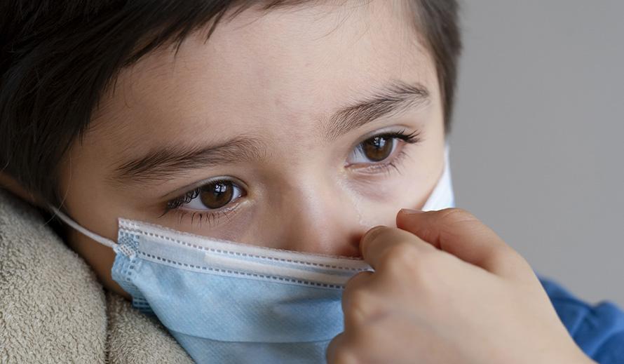 A Hispanic boy looks despondent during the coronavirus pandemic.