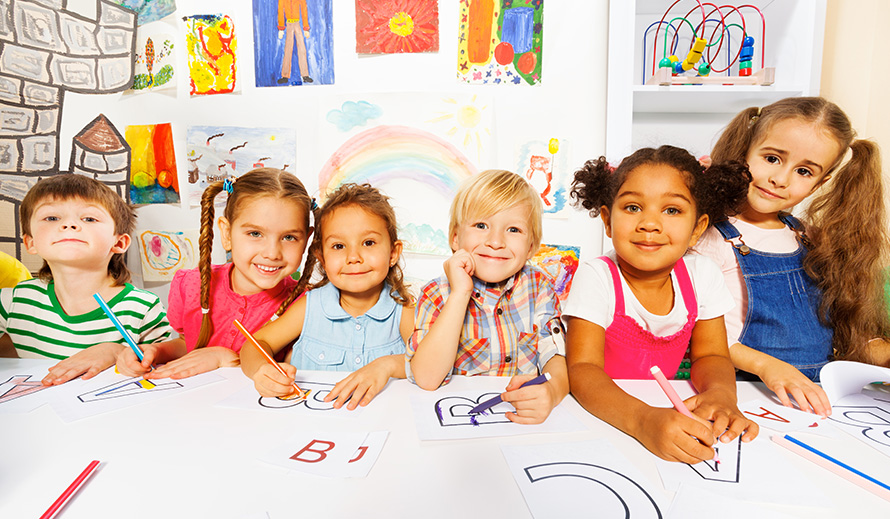 Photo of a group of smiling boys & girls at a table coloring in letters.