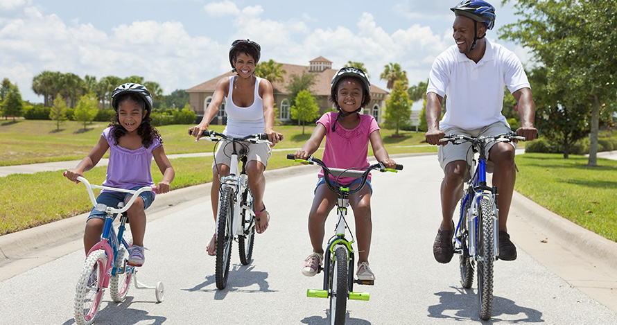 An African American family takes a summer bike ride.