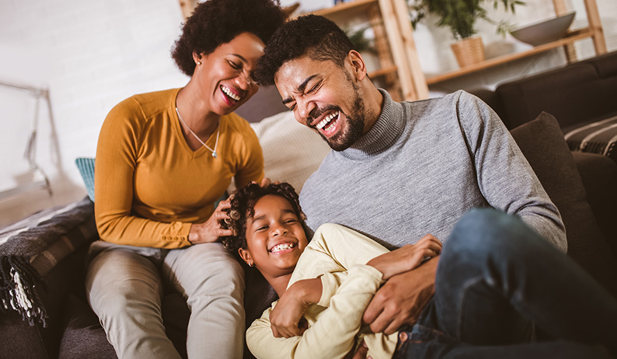 African-American father and mother tickle daughter at home.