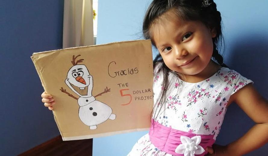 Una niña muestra un signo de agradecimiento al  Five Dollar Project.