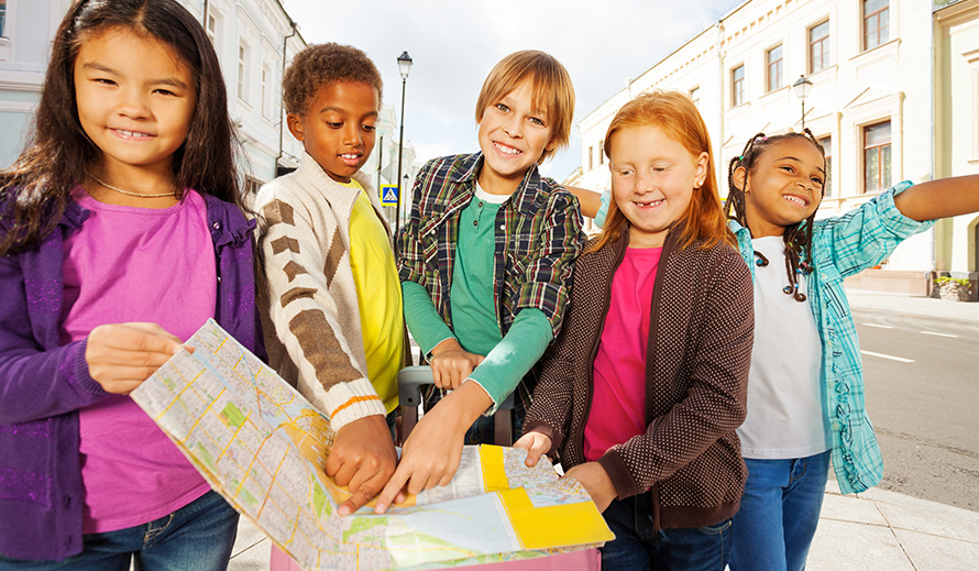 Group of children on the sidewalk looking at a map