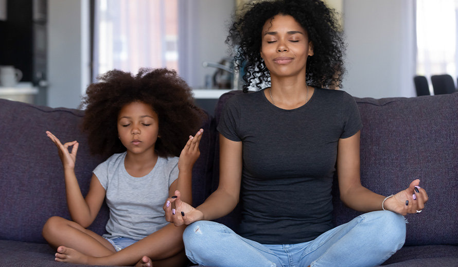 A mom and daughter practice yoga.