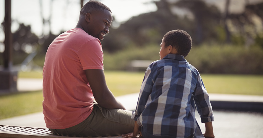 An African American father speaks with his son on a bench.
