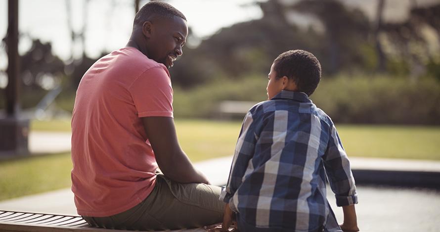 Un padre afroamericano habla con su hijo en un banco.