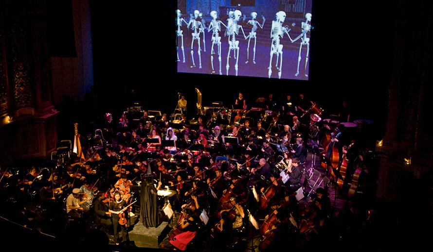 Una orquesta en escena bajo una pantalla gigante donde se proyectan esqueletos danzantes.