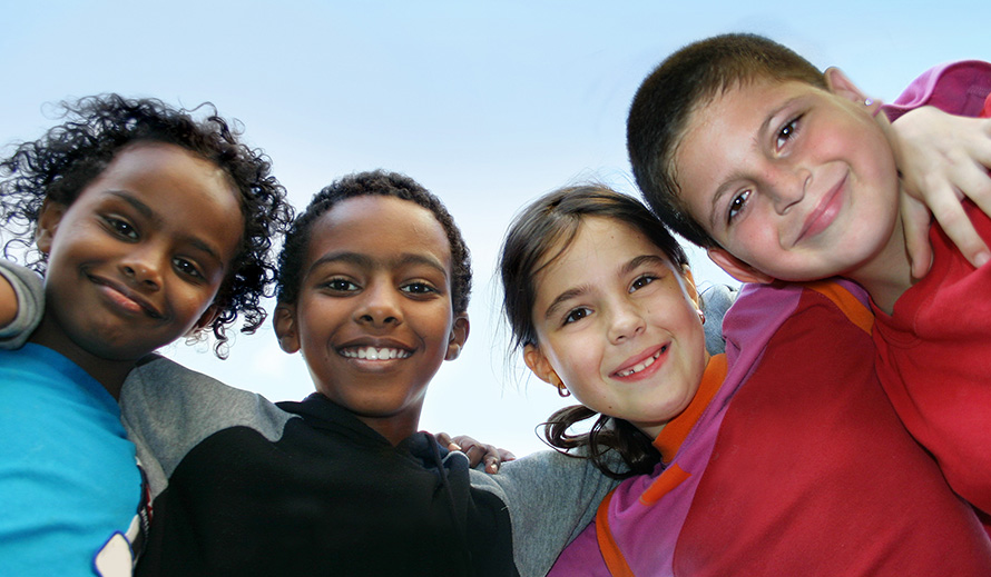 Diverse children smiling with arms around each other