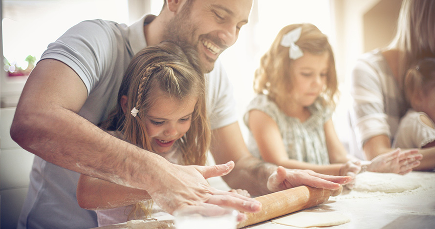 Un padre prepara una comida con sus hijos.