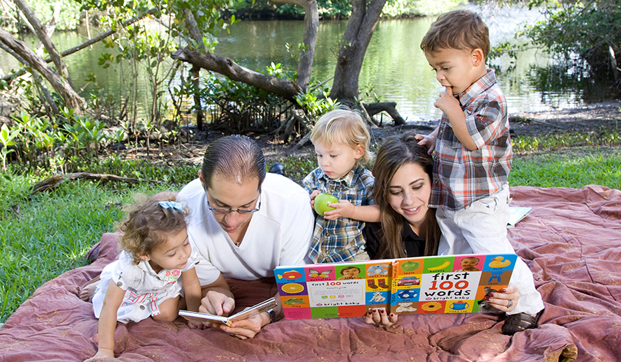 Family reading on a blanket at the park.