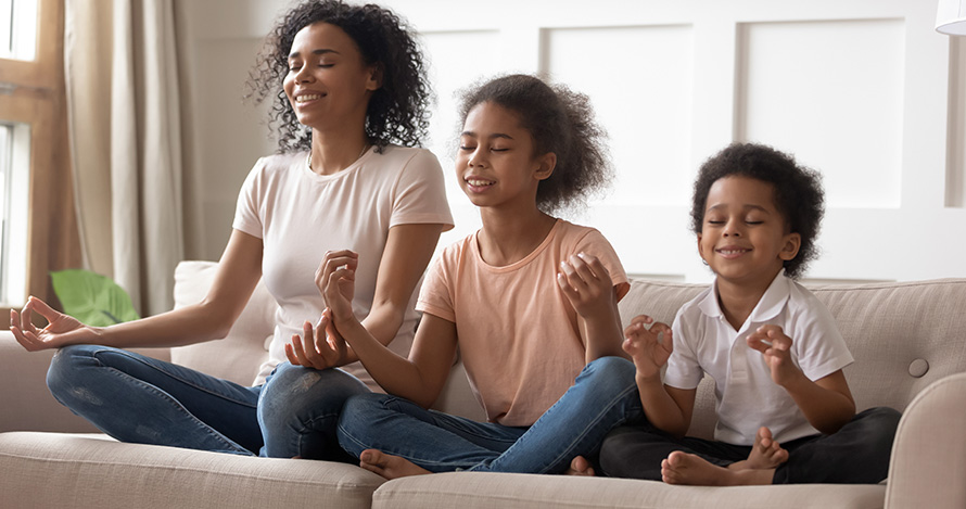 An African American mother meditates with her two young children.
