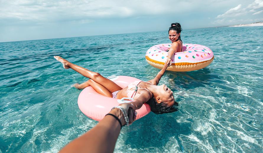 Dos chicas disfrutan del agua en flotadores.