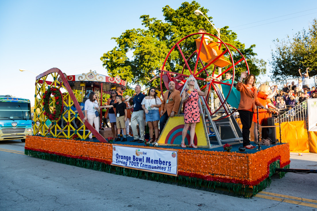 Photo of a float carrying a mini ferris wheel and Orange Bowl Committee Members during a parade.