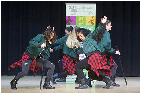 An all-girl teen dance troupe auditioning on stage.