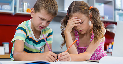 Frustrated young brother and sister doing homework
