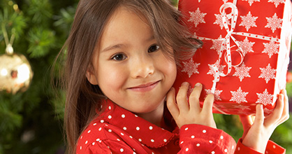 Smiling pajama-clad little girl holding a wrapped gift in front of a Christmas tree