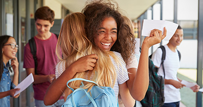 High school students happily hugging each other, with acceptance letters in their hands