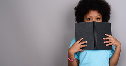 A shy African American girl hides behind a book.