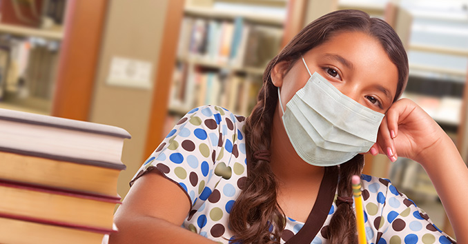 Young girl wears face mask while doing school work