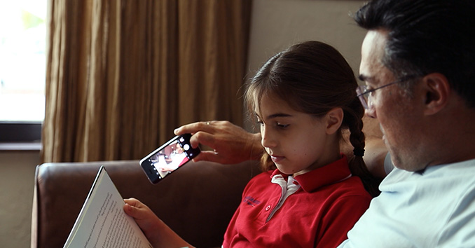 Father taking a selfie while reading to his daughter