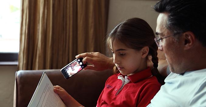 Padre tomando un selfie mientras lee con su hija