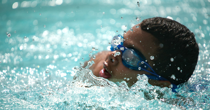 Boy with goggles swimming in pool
