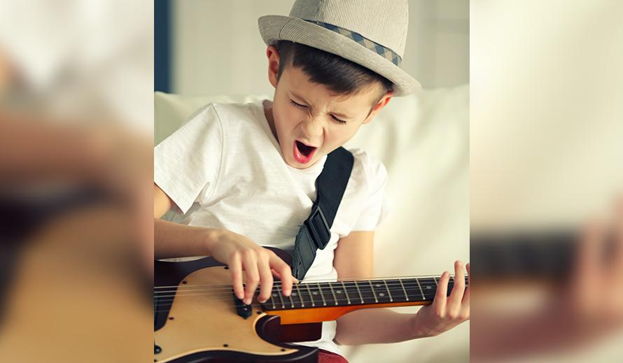 Little boy singing and playing a guitar.