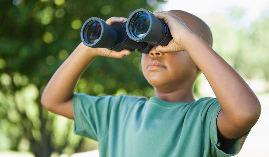 Niño mirando a través de binoculares.