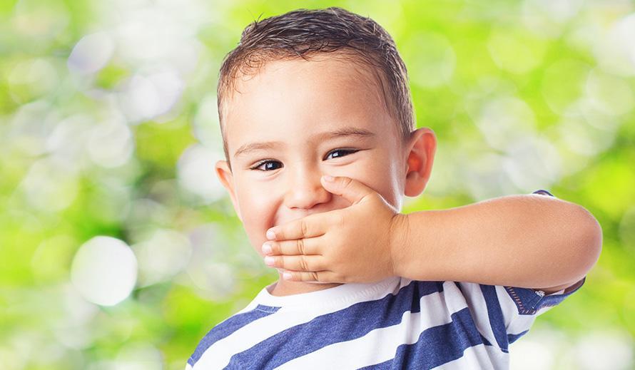 Niño pequeño sujetando su mano sobre la boca.