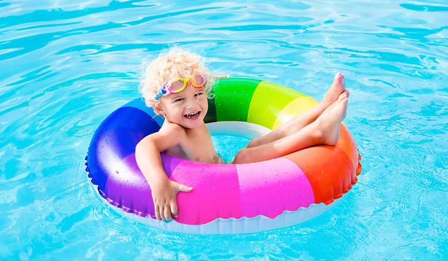 Un niño flota feliz en una piscina sobre un salvavidas a rayas de arco iris.
