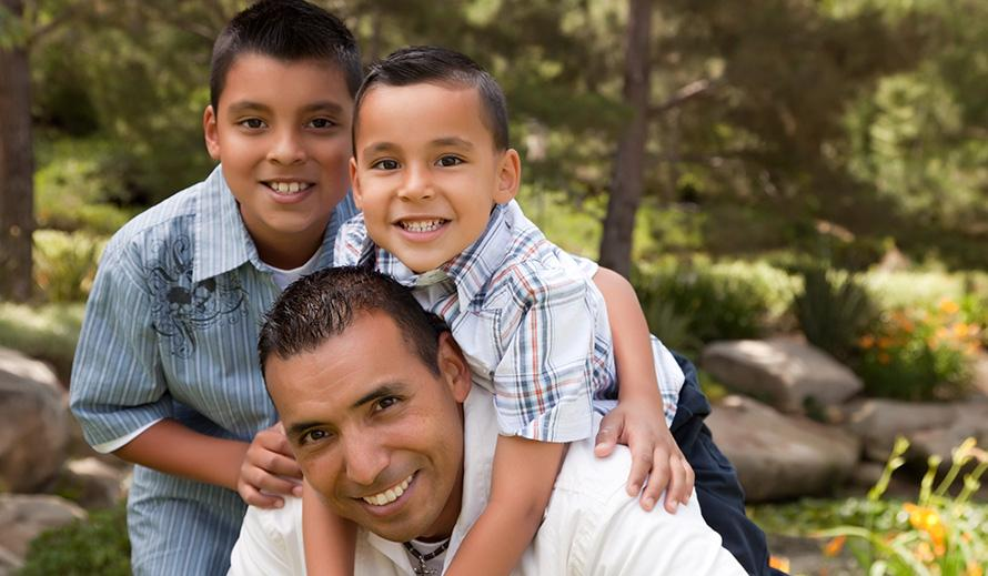 Happy dad and sons outdoors.