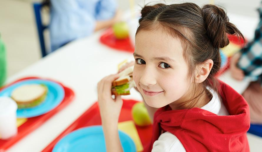 A little girl smiles while eating school lunch.