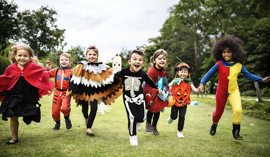 Kids in Halloween disguises run.