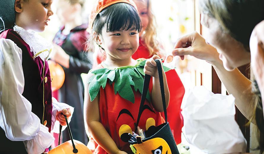 A little girl dressed as a pumpkin gets candy on Halloween.