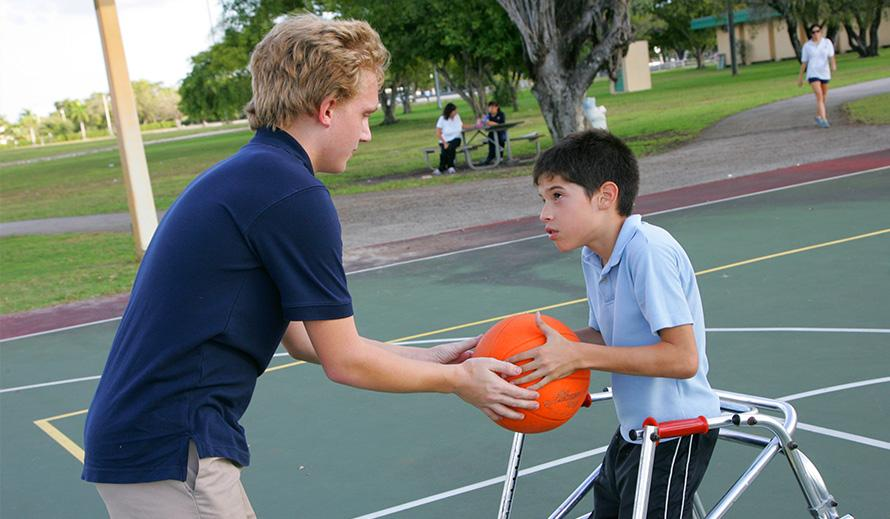 Typically-abled boy passes basketball to special needs boy in a walker on a basketball court